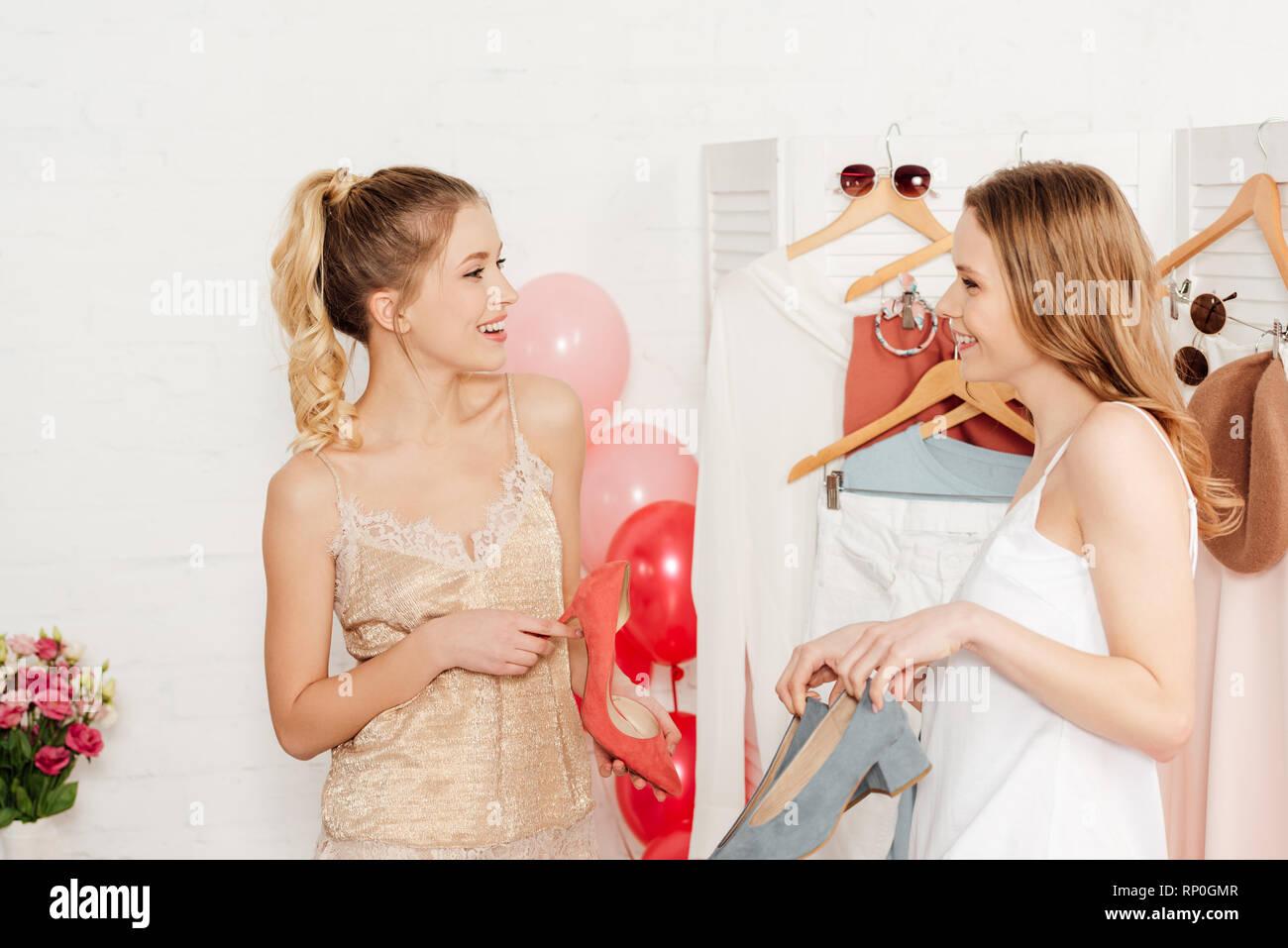 beautiful smiling girls talking while choosing footwear in wardrobe - Stock Image