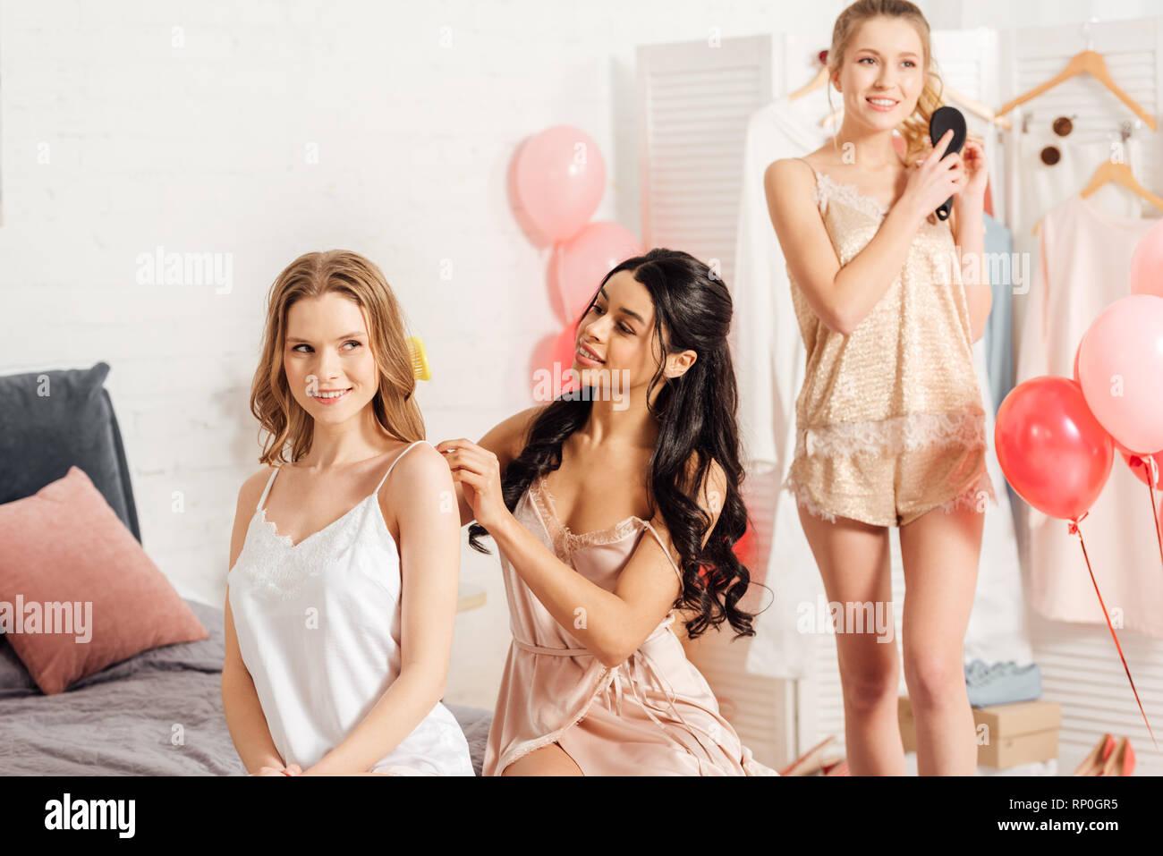 beautiful smiling multicultural girls in nightwear brushing hair during pajama party - Stock Image