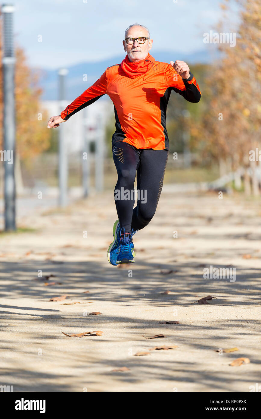 Senior man jumping in a city park ( lifestyle ) - Stock Image