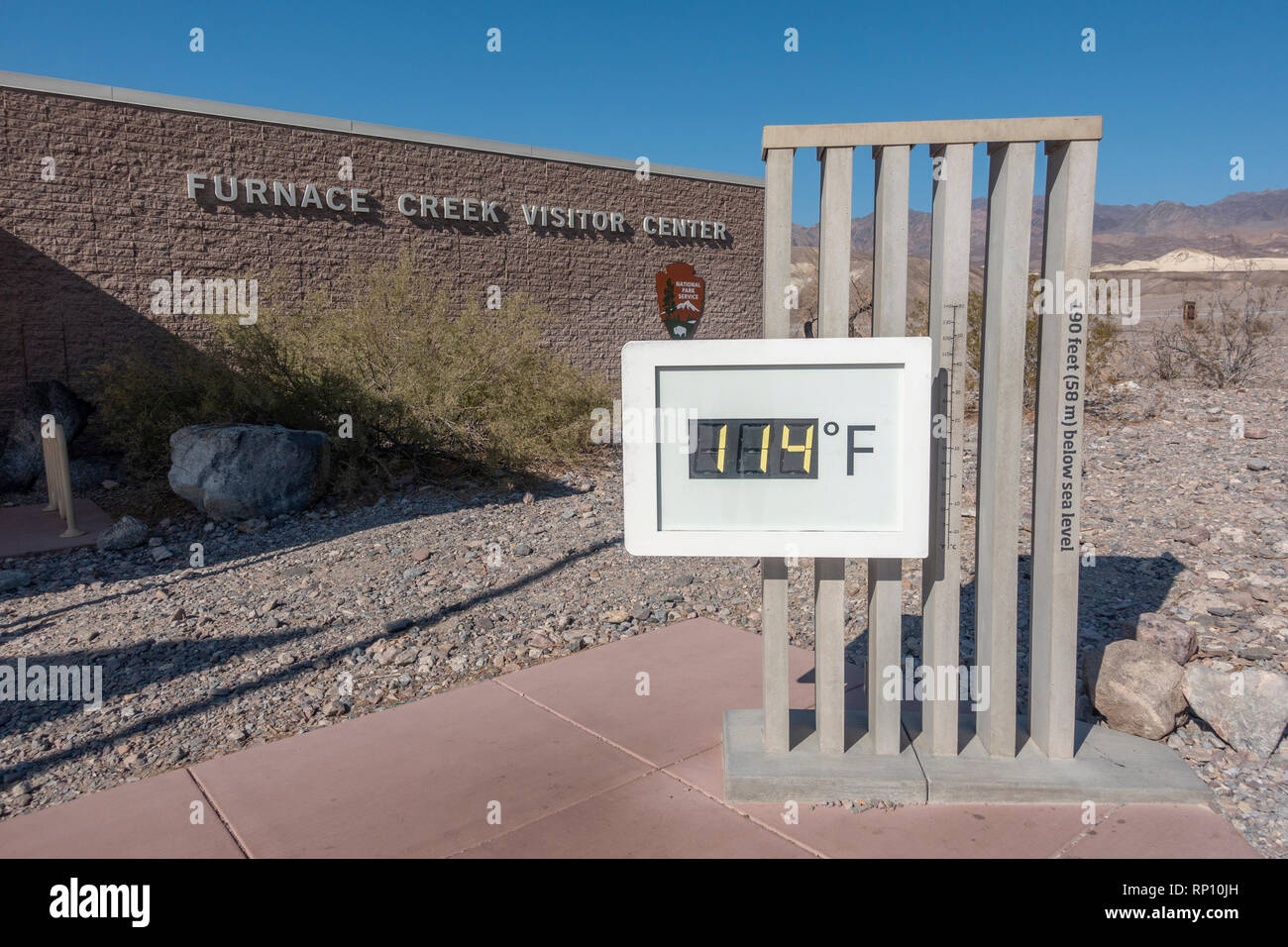 Temperature gauge showing 114℉ (45.6°C) outside the Furnace Creek Visitor Center, Furnace Creek, California, United States. - Stock Image