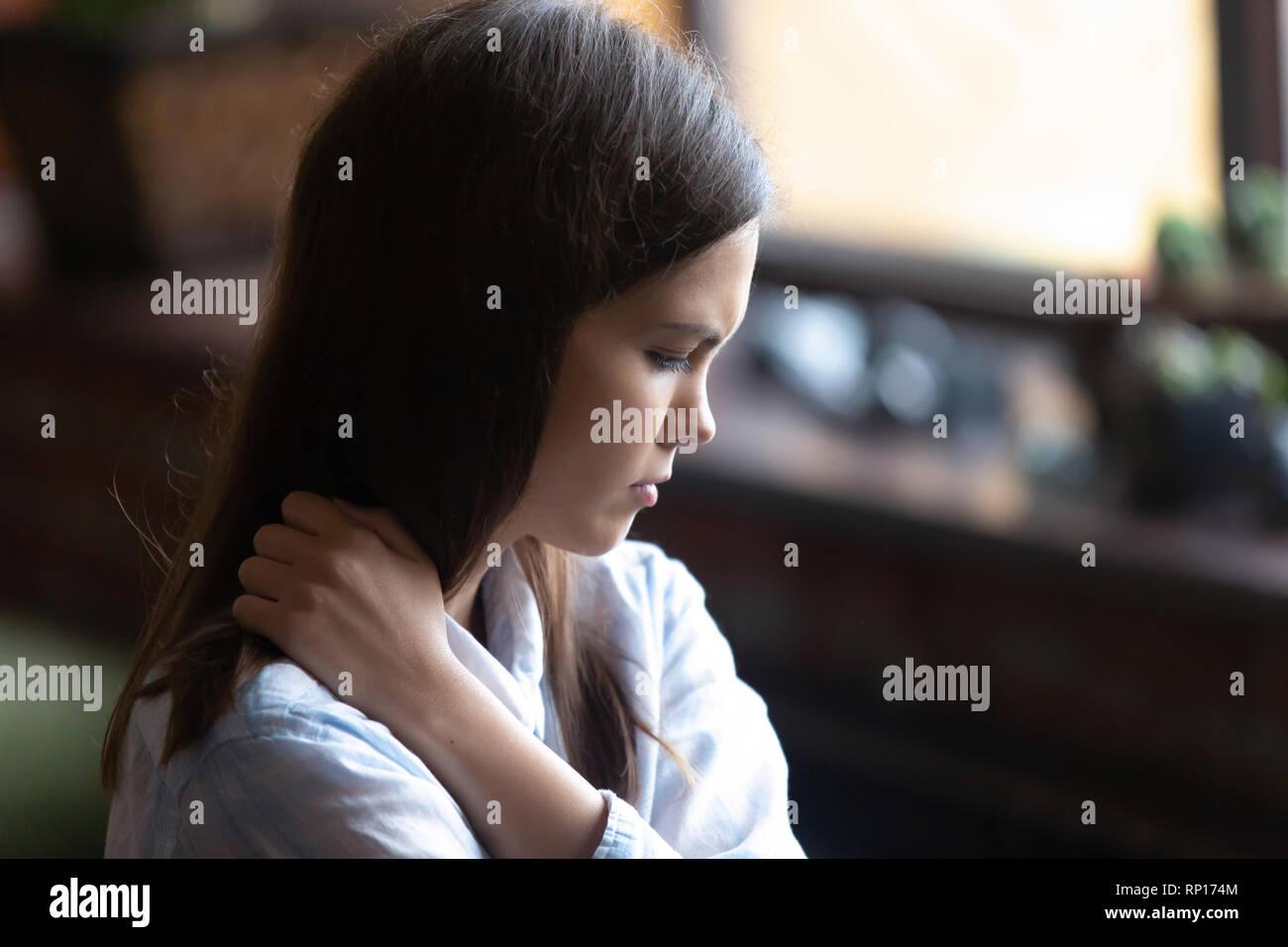 Sad and lonely female sitting alone indoors - Stock Image