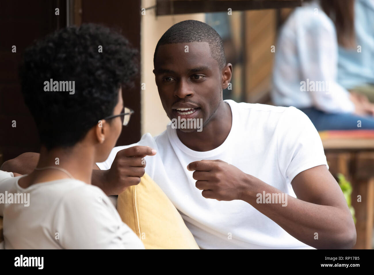 Black married couple talking resting in summer cafe - Stock Image