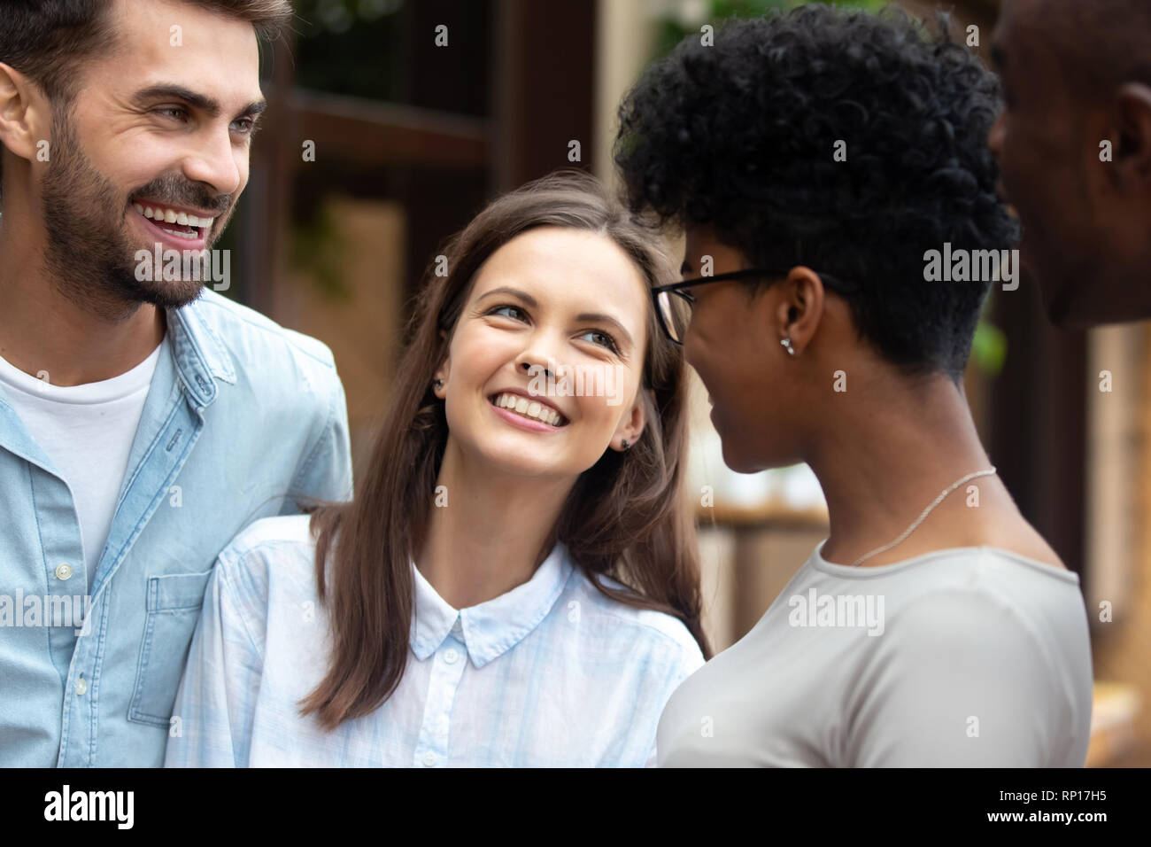Diverse friends girls and guys standing laughing outdoors - Stock Image
