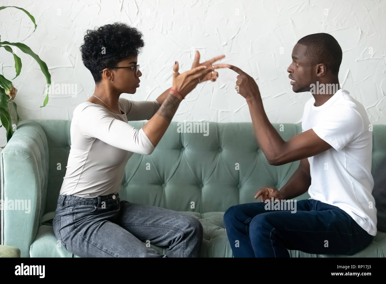 Black african couple quarrelling sitting on couch - Stock Image