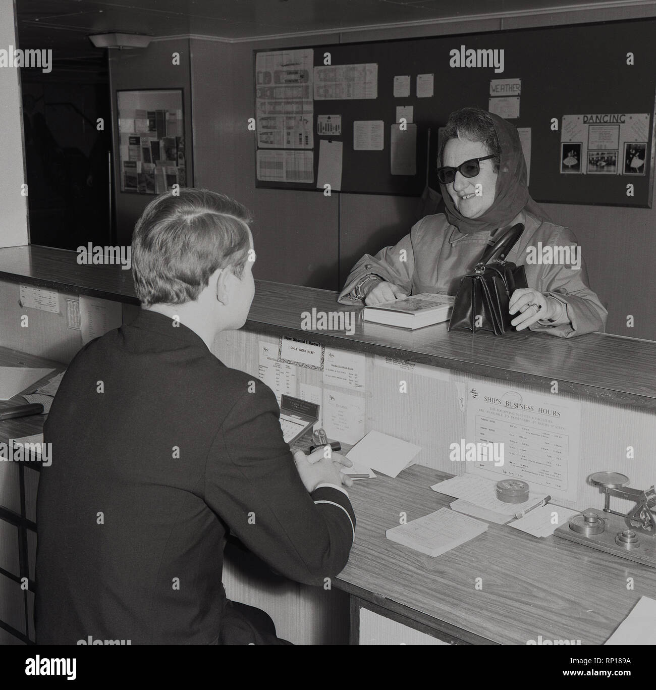 1950s, a lady passenger travelling on a Union-castle steamship talking to a uniformed ship's officer at the information desk or inquiry bureau. - Stock Image