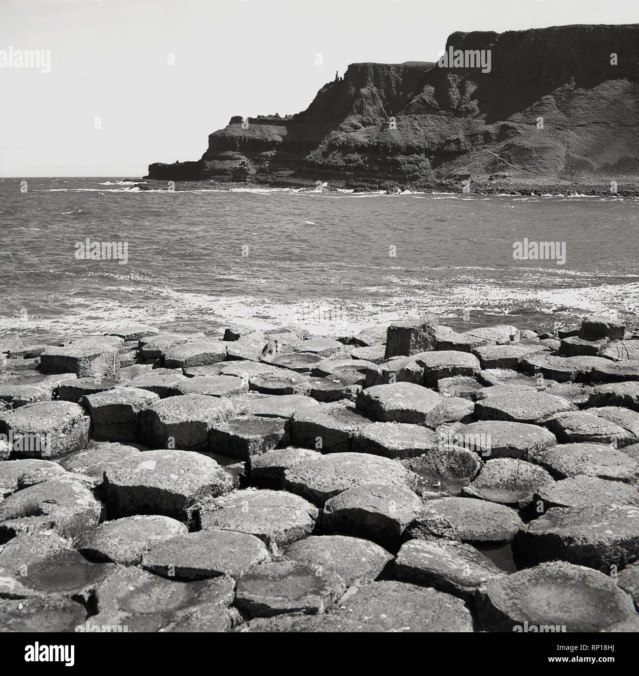 1950s, historical picture showing the ancient interlocking hexagonal basalt columns or stones at the sea's edge at the Giant's Causeway, Co. Antrim, located on the rugged North Atlantic Coast, Northern Ireland, UK. Stock Photo