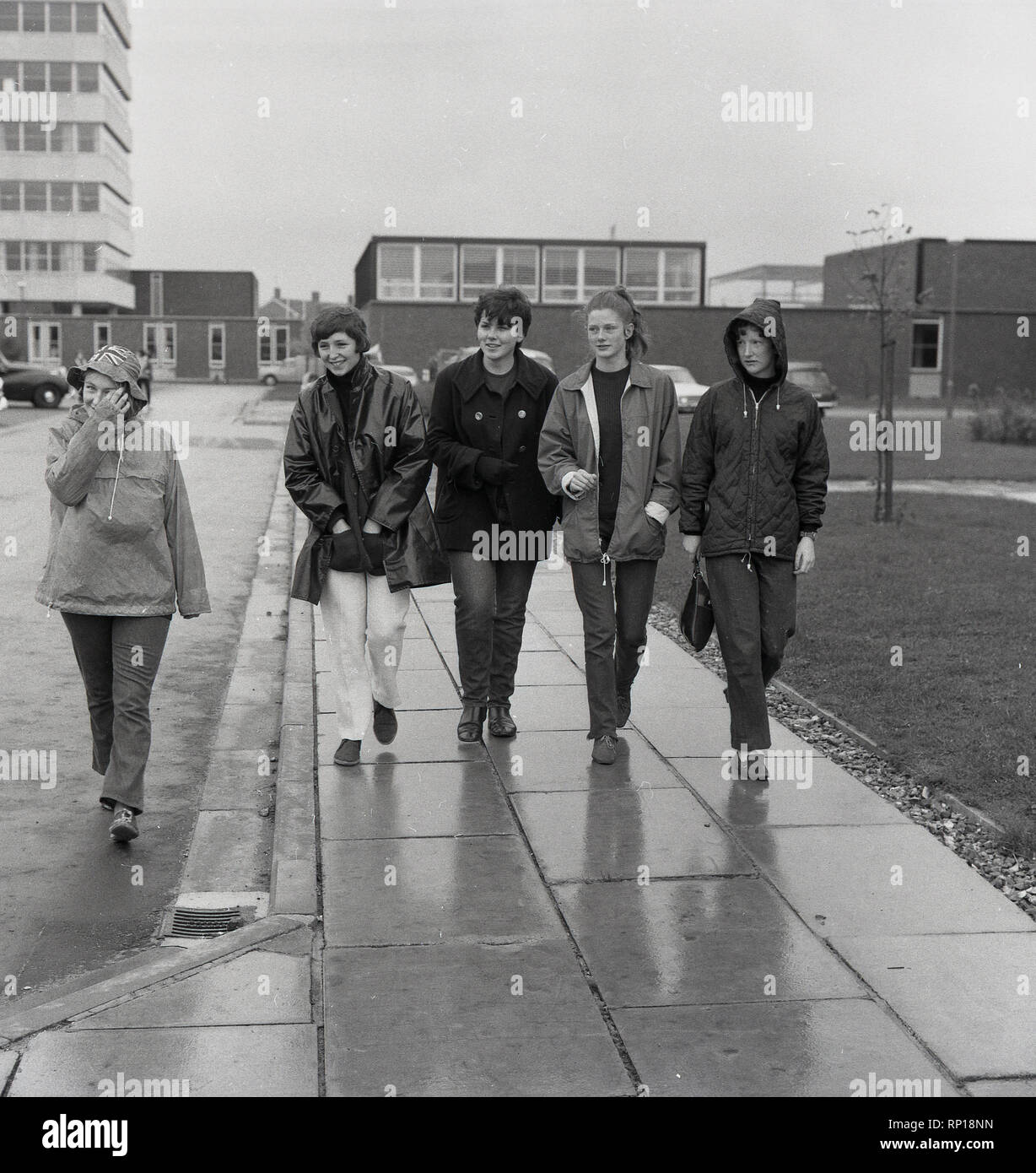 1967, historical, five young women wearing anoraks setting  off in wet, rather miserable weather, on a long overnight fundraising or sponsored walk to Oxford for the famine relief charity, Oxfam, which was celebrating its 25th year with a series of events. Stock Photo
