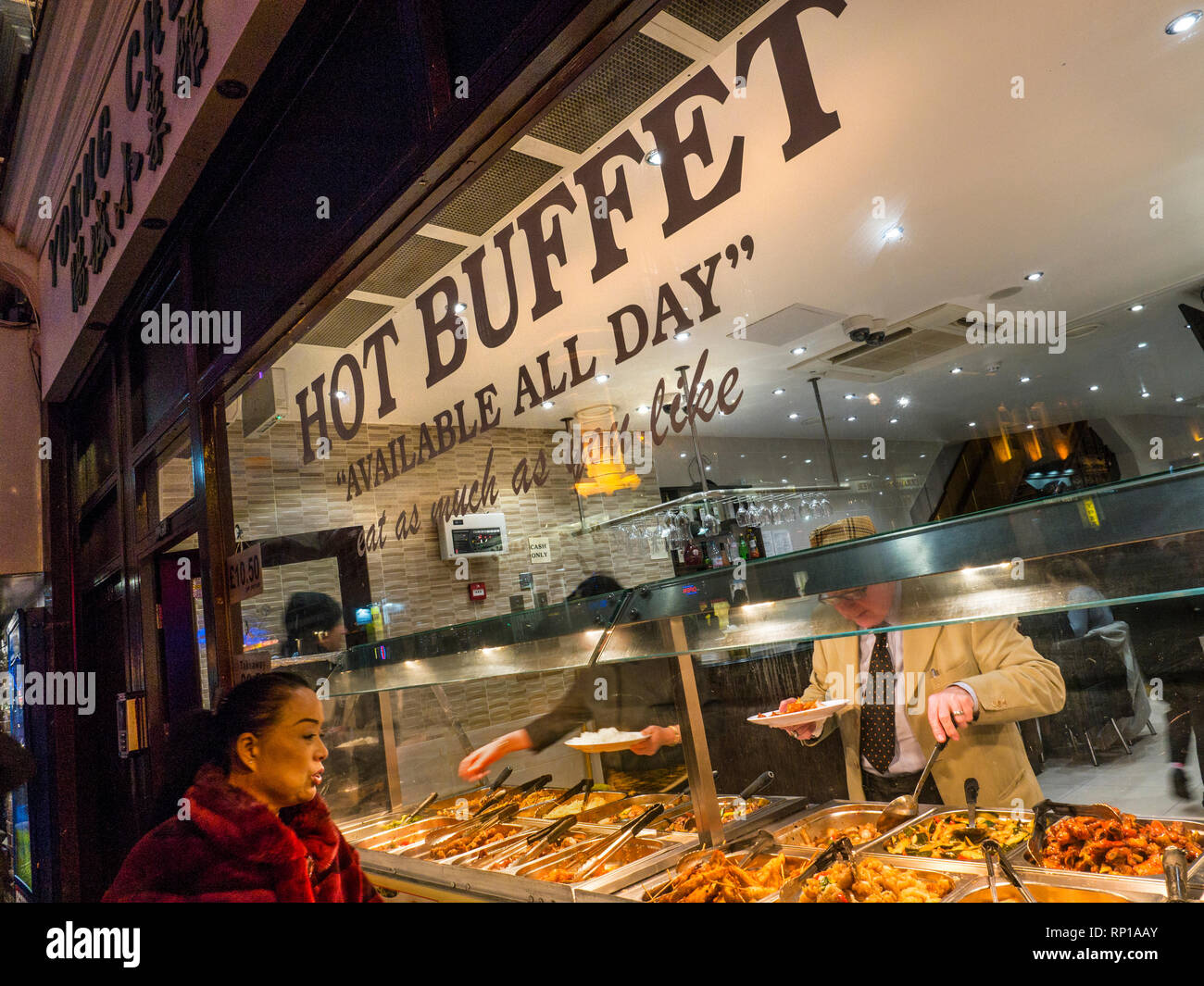 Chinese hot buffet selection 'eat as much as you like' window, with oriental woman looking appreciatively at the Chinese food varieties on open display.  Wardour Street Chinatown Soho London UK Stock Photo