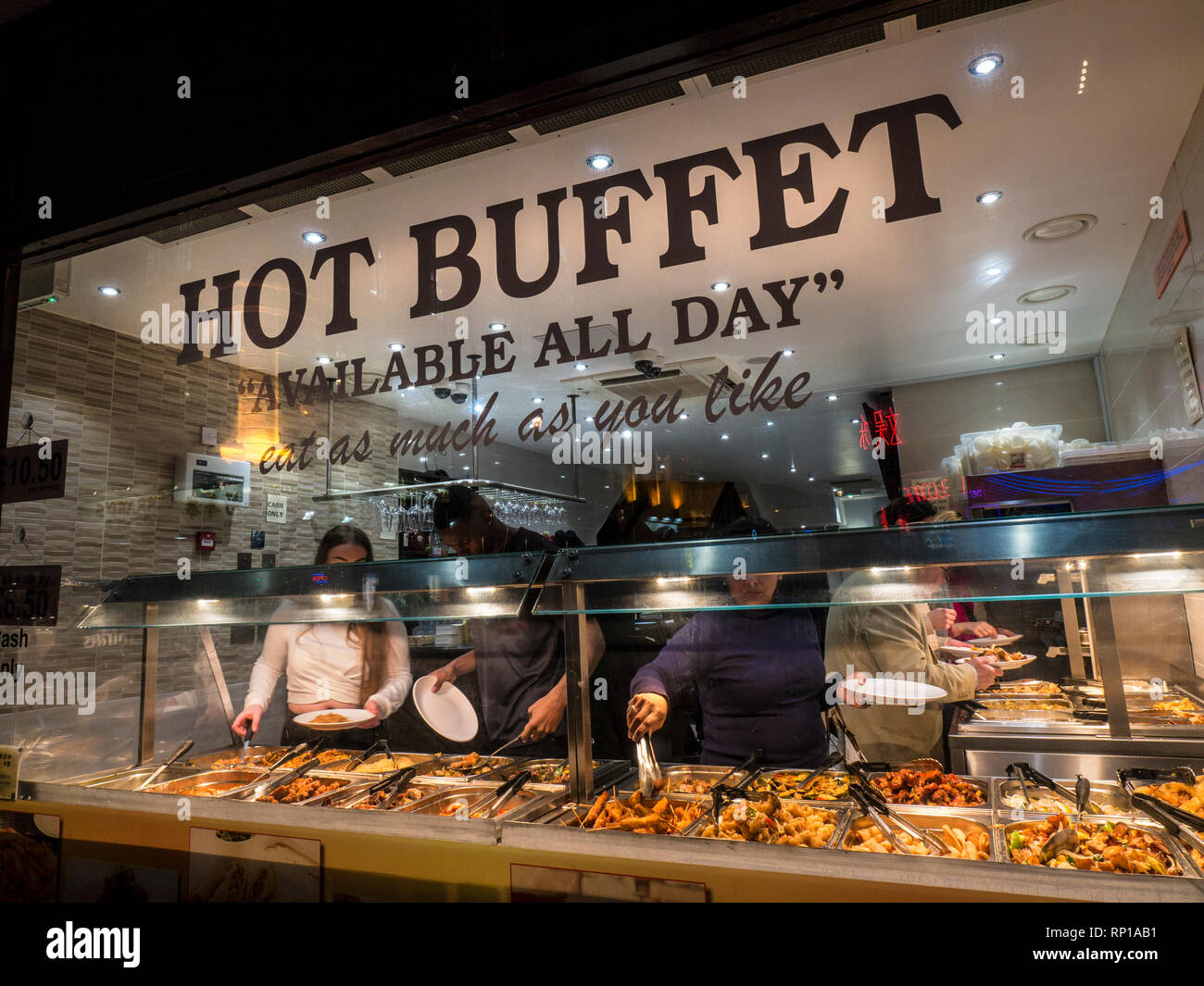 Chinese hot buffet selection 'eat as much as you like' window with patrons selecting a variety of Chinese food Wardour Street Chinatown Soho London UK - Stock Image