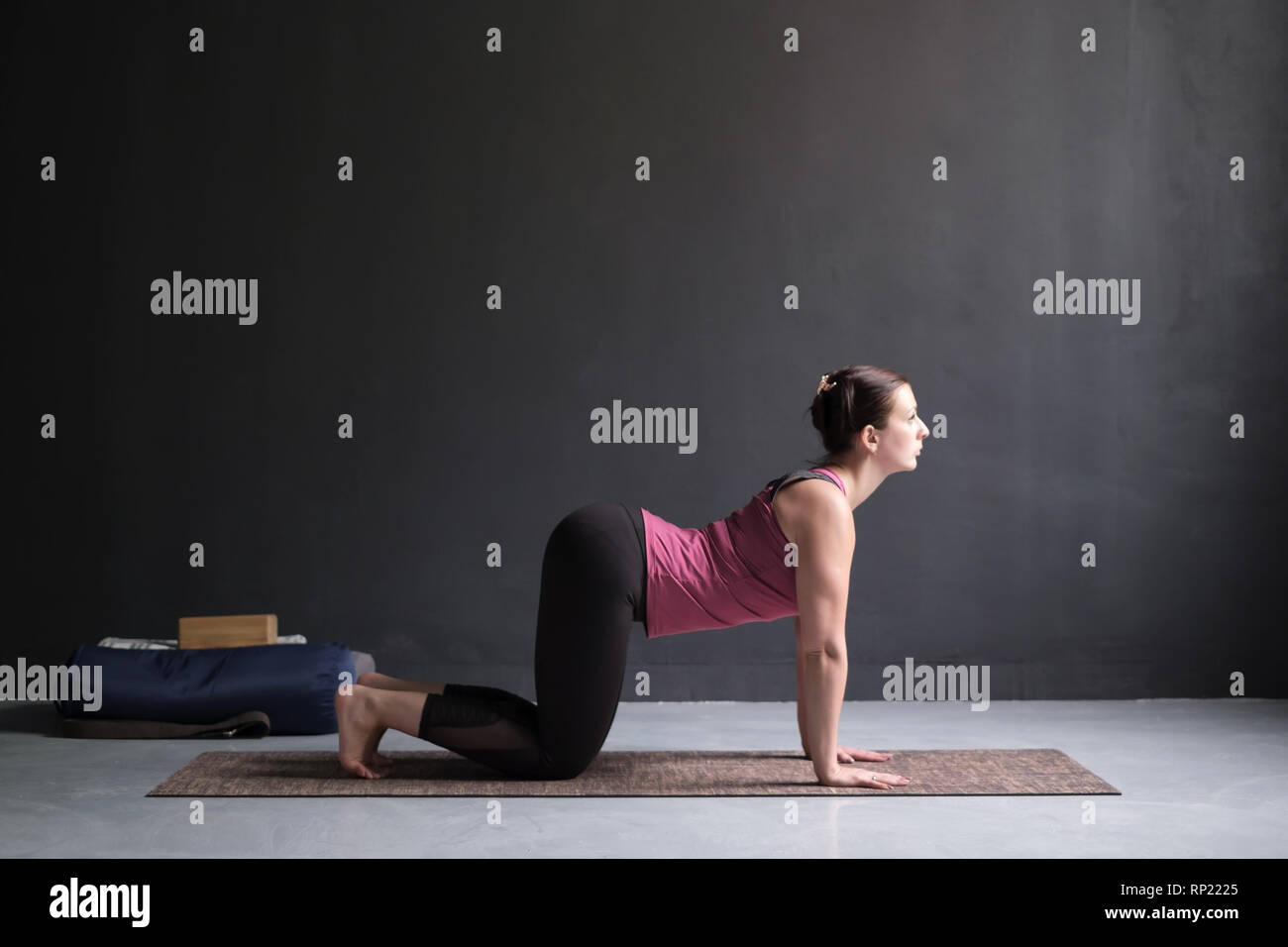 Woman working out ag doing yoga or pilates exercise. Cat, Marjaryasana Stock Photo