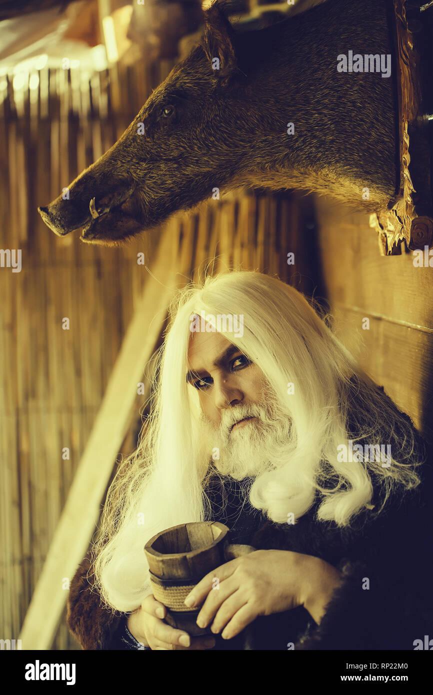 Druid and stuffed boar head - Stock Image