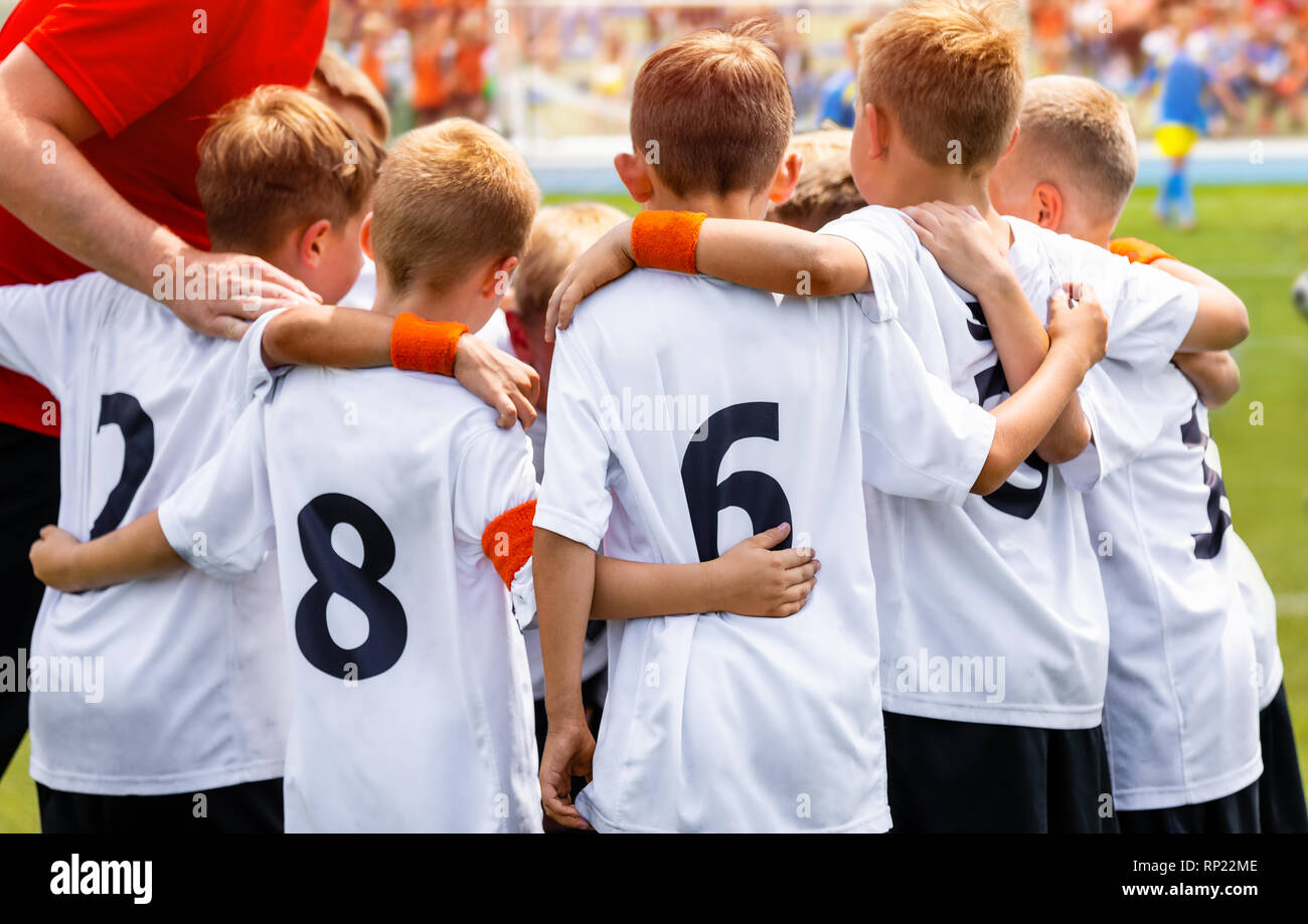 Young Boys In Football Team. Group Of Children In Soccer Team. School Football Coach's Pregame Speech. Coaching Youth Sports - Stock Image