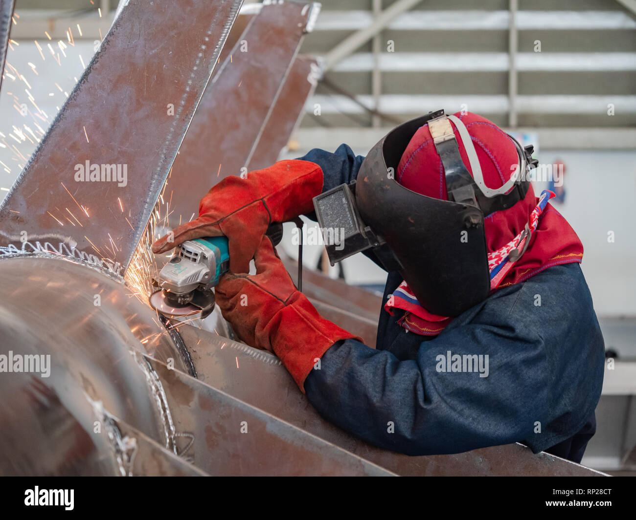 Industrial worker wearing a welding mask using an angle grinder on a steel structure. Stock Photo