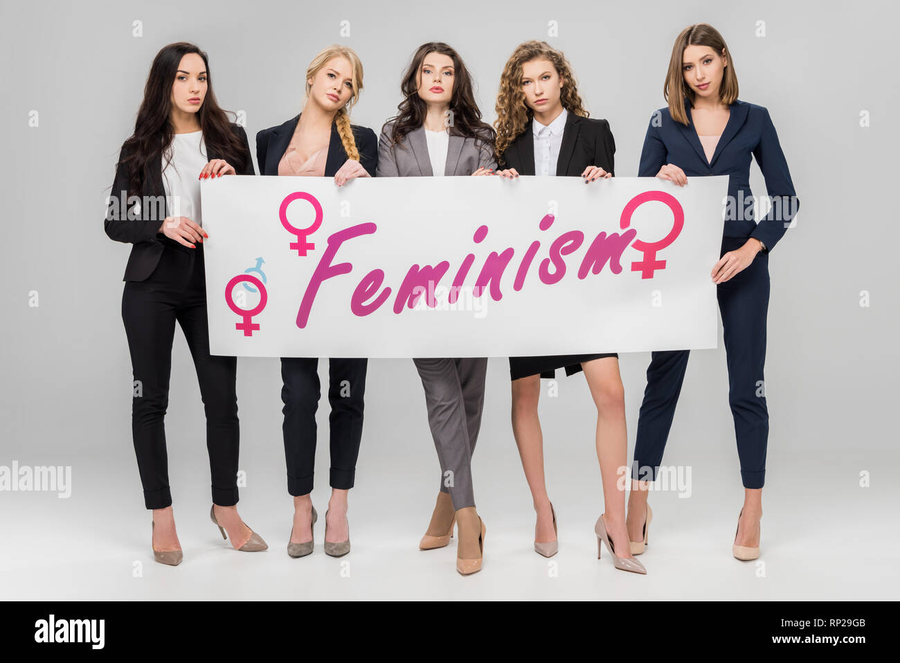 attractive businesswomen holding  large sign with feminism lettering on grey background - Stock Image