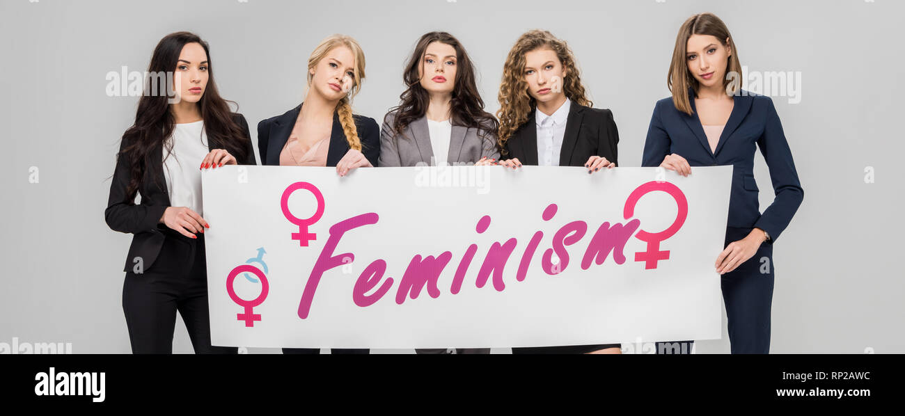 attractive businesswomen holding  large sign with feminism lettering isolated on grey - Stock Image