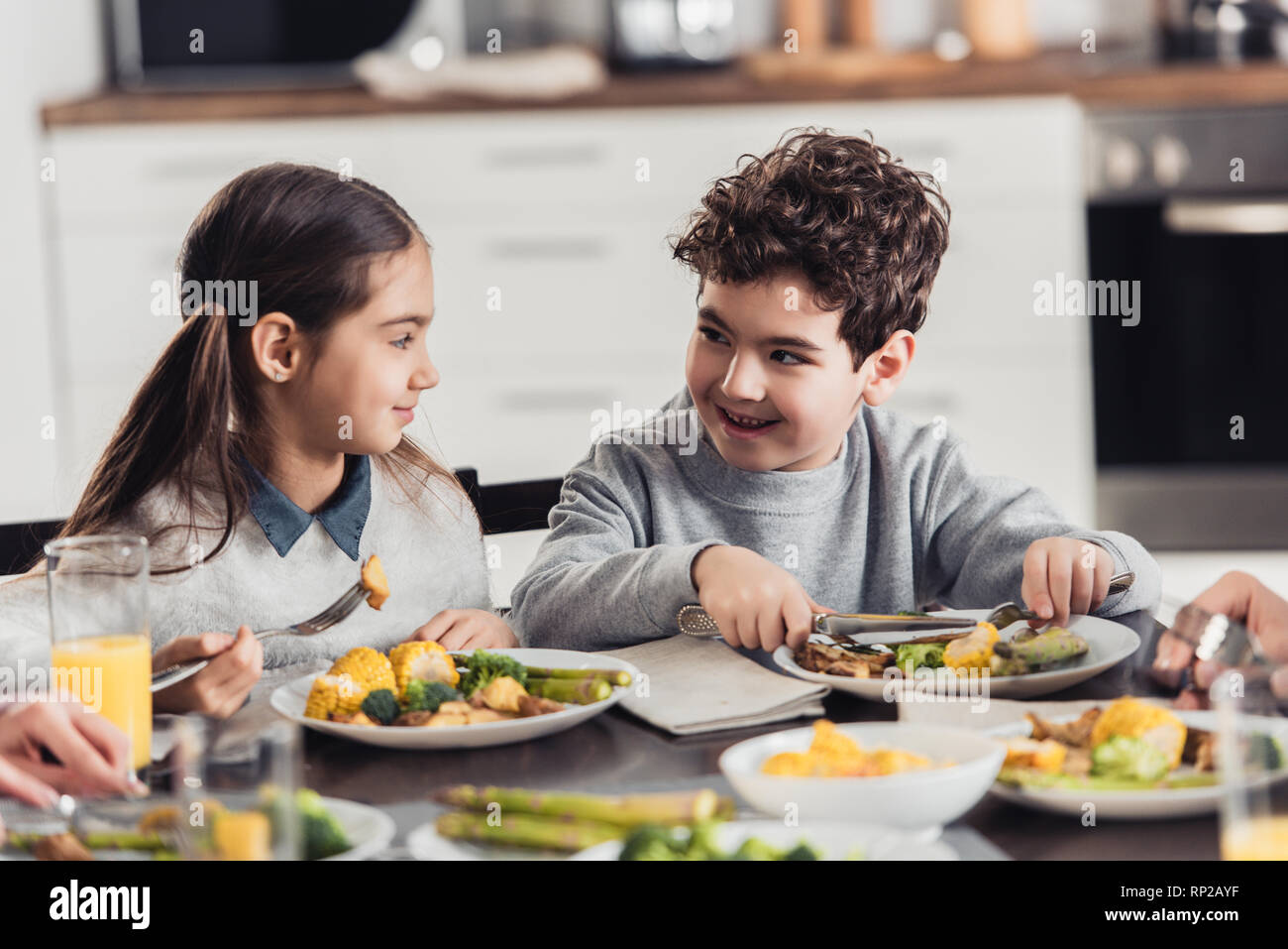 cheerful sister looking at brother while having lunch at home Stock Photo