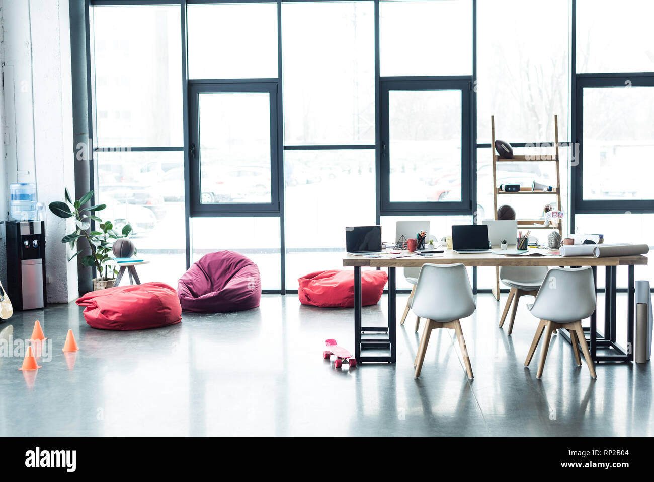 modern design of spacious loft office with bean bag chairs and table with laptops - Stock Image