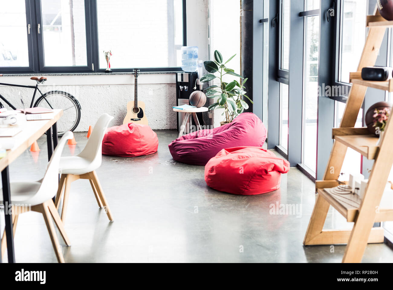 modern design of spacious loft office with bean bag chairs, wooden rack and table - Stock Image