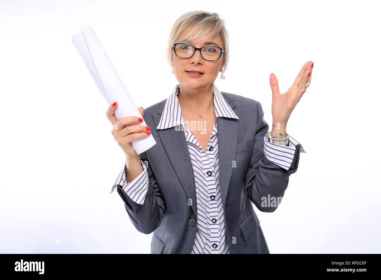A middle-aged teacher, 40 years old, in a white striped shirt, gray suit and glasses, with a red manicure, holding white paper on a white background - Stock Image