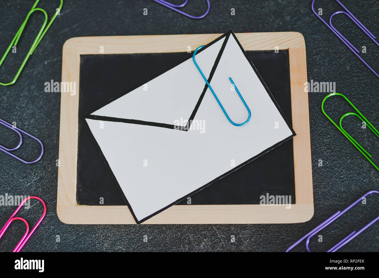 email envelope on blackboard with paper clip symbol of attachment, metaphor of internet communication - Stock Image