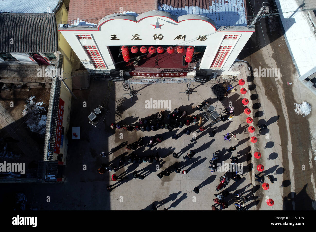 (190220) -- WUXIANG, Feb. 20, 2019 (Xinhua) -- Aerial photo shows villagers watching performance at an open air theater in Wangzhuanggou Village, Wuxiang County of north China's Shanxi Province, Feb. 16, 2019. For generations, residents of Wangzhuanggou Village barely scraped a living as a result of geographical isolation. However, a great change has been made since a series of poverty relief programs were launched in 2014. The whole village has been lifted out of poverty by the year of 2018 with the per capita annual income rising to 6,100 yuan (907 U.S. dollars) that enables villagers to spe - Stock Image