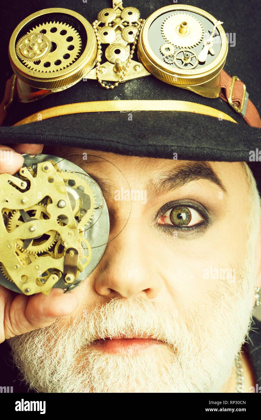 Bearded man looks through gear - Stock Image