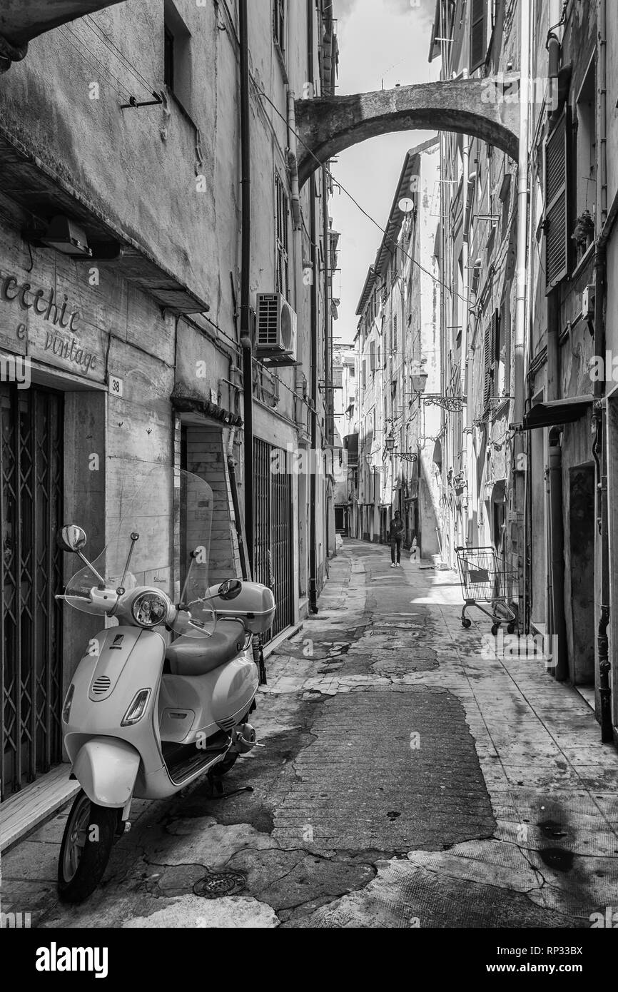 Black White picture of a scooter parked in the narrow street Via Bezzecca in the center of the Italian town San Remo. - Stock Image