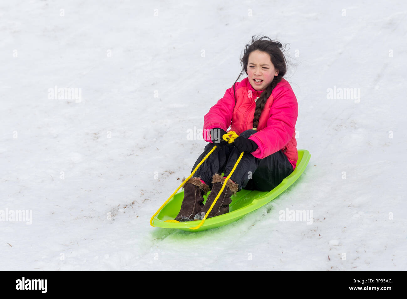 Young Asian girl with pink hat and jacket in snow riding sled Stock Photo