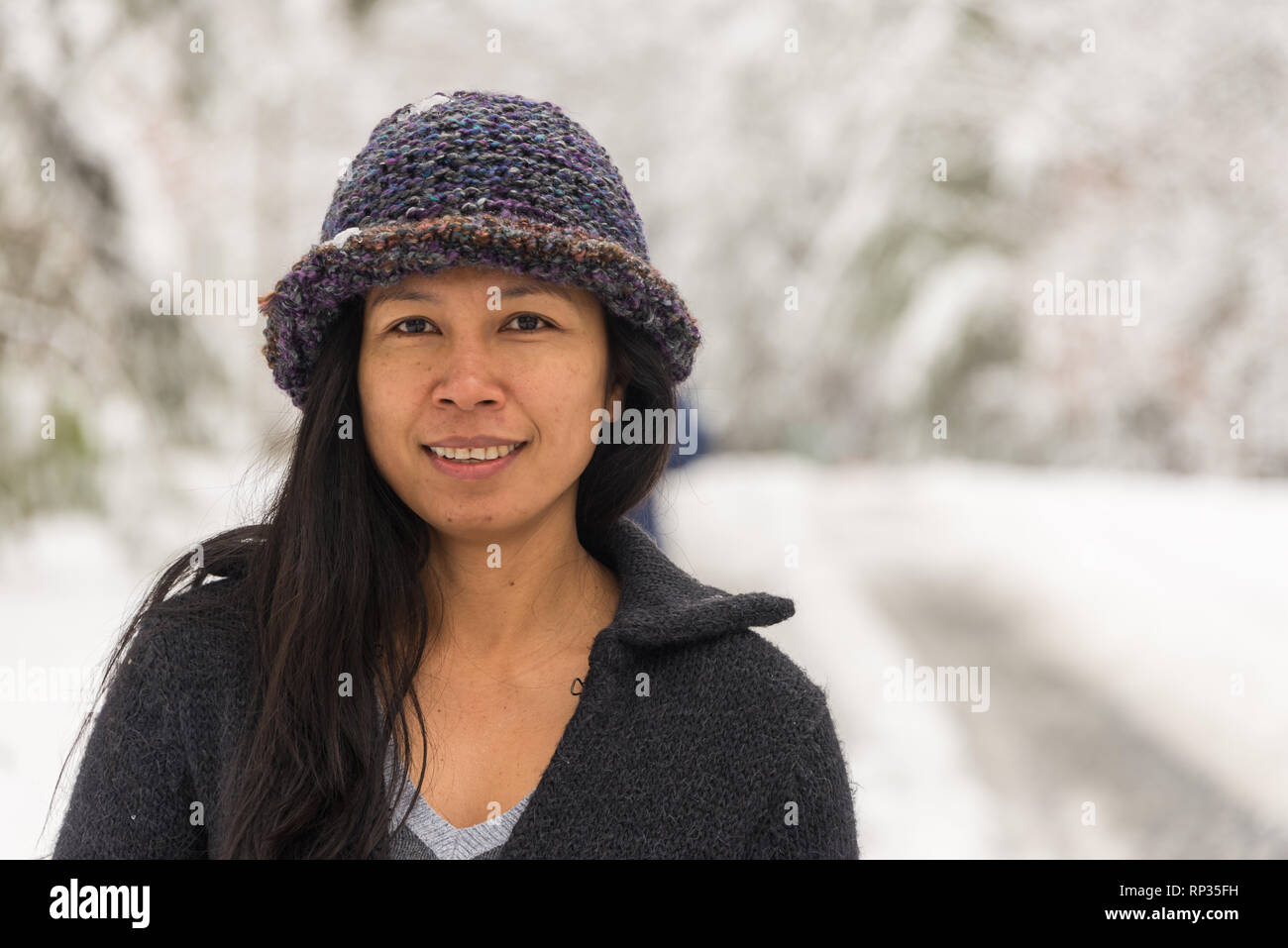 9dec853de7d Asian woman in hat standing in front of trees after snow storm Stock ...