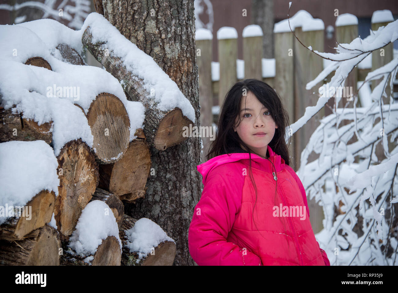 Young Asian girl in pink coat standing next to snow covered log pile - Stock Image