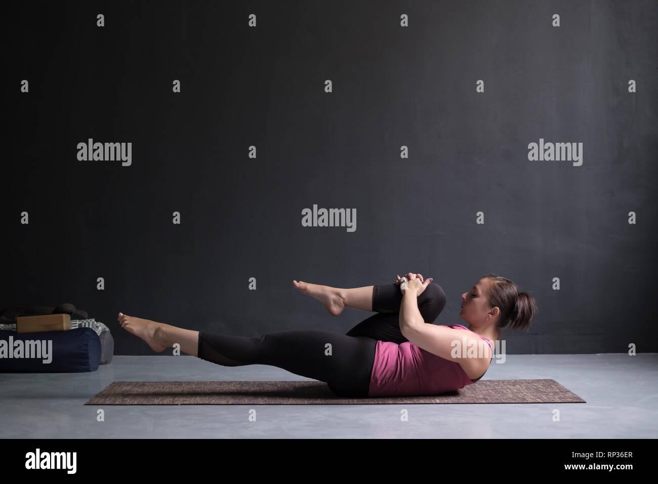 Woman doing Hatha Yoga asana Ardha pawanmuktasana or knees to chest pose. - Stock Image