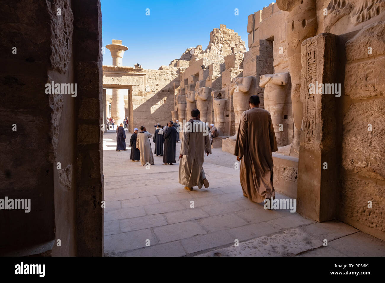 Luxor temple, egyptian men in traditional clothes in the ruins - Stock Image