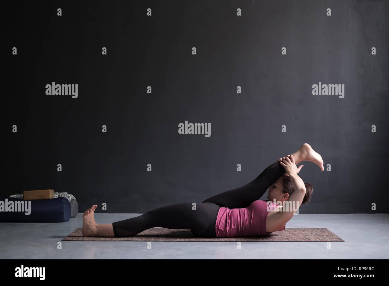 Woman doing Yoga asana Supta padangusthasana or reclining hand to big toe pose - Stock Image