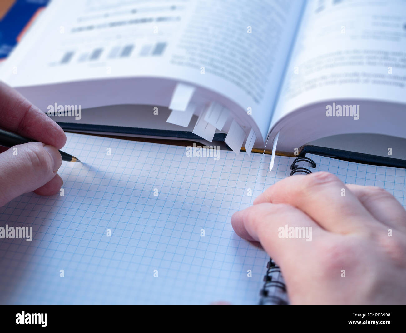 closeup image of left handed student with pen above exercise book making memos . blurred book on background - Stock Image