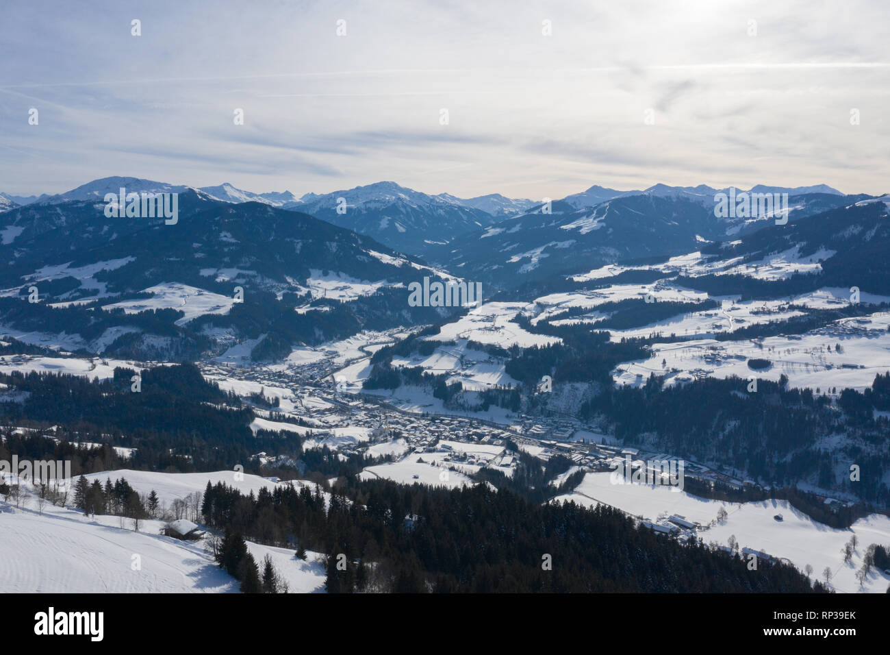View from a drone on a small village among winter mountains covered with forests and snow in Alps. - Stock Image