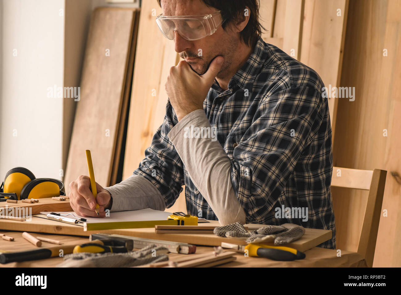 Carpenter planning DIY project in his small business