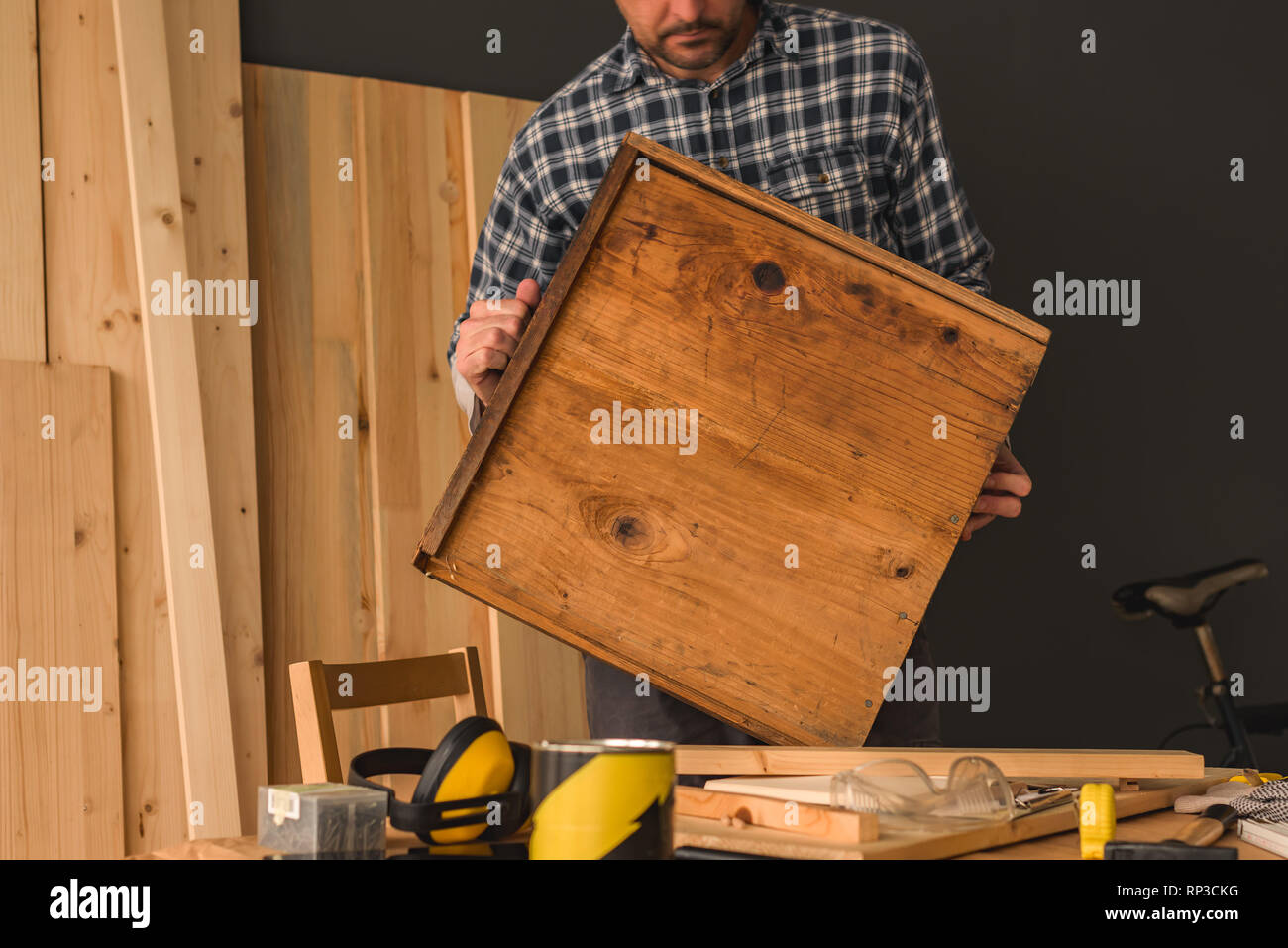 Carpenter repairing old wooden drawer in small business woodwork workshop Stock Photo