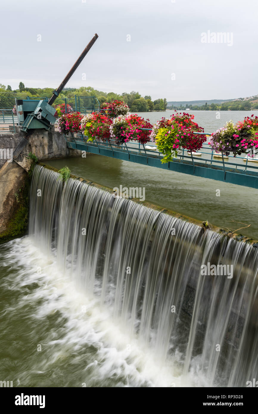 The weir of Kir lake, an artificial lake located south west of Dijon (Burgundy, France) with beautiful flowers on a cloudy day in summer Stock Photo