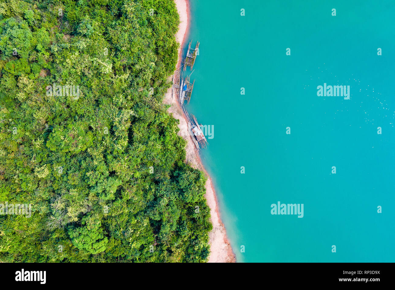 (View from above) Stunning aerial view of a a green coast of a tropical island with some traditional fishing boats in Nam Ngum Reservoir. Stock Photo