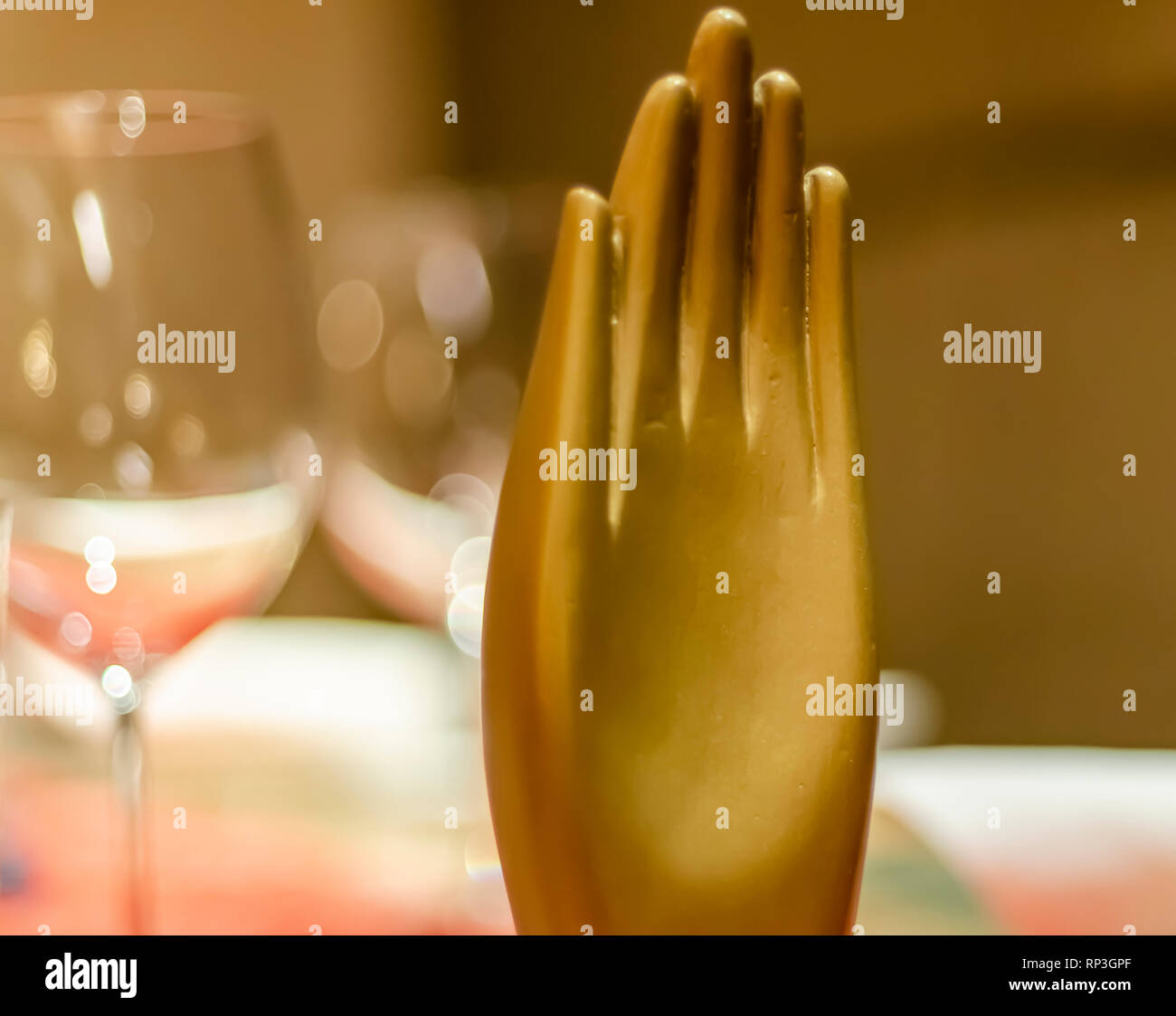 A ceramic hand used as a visual cue to signify that a table in a restaurant is already booked/reserved/taken. Wait! Stop! Warning! Hold! - Stock Image