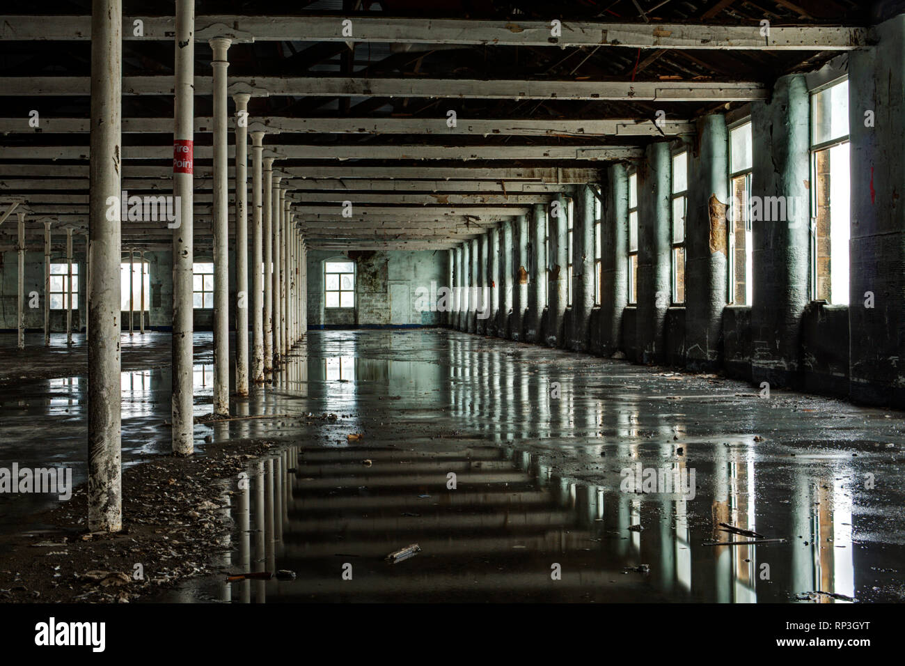 Reflections from a waterlogged floor in a derelict mill Stock Photo