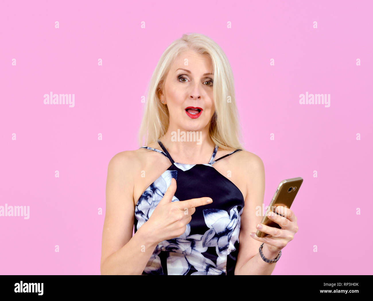 Attractive woman pointing at her mobile phone with a look of disbelief at whats just come in on her phone - Stock Image