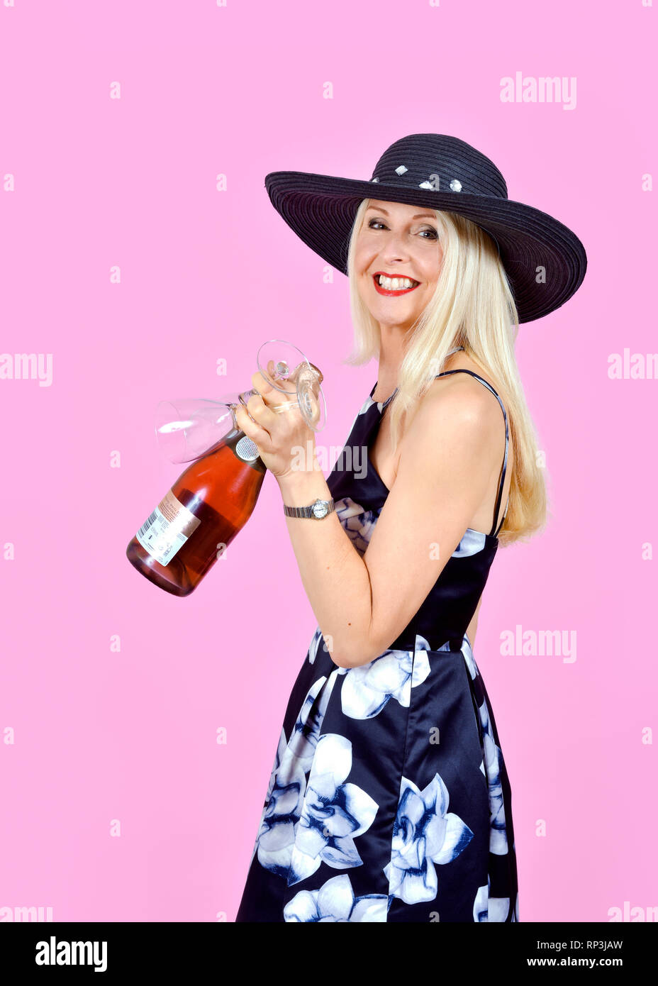 Happy, attractive blonde woman carrying a bottle of wine and a couple of wine glasses - Stock Image