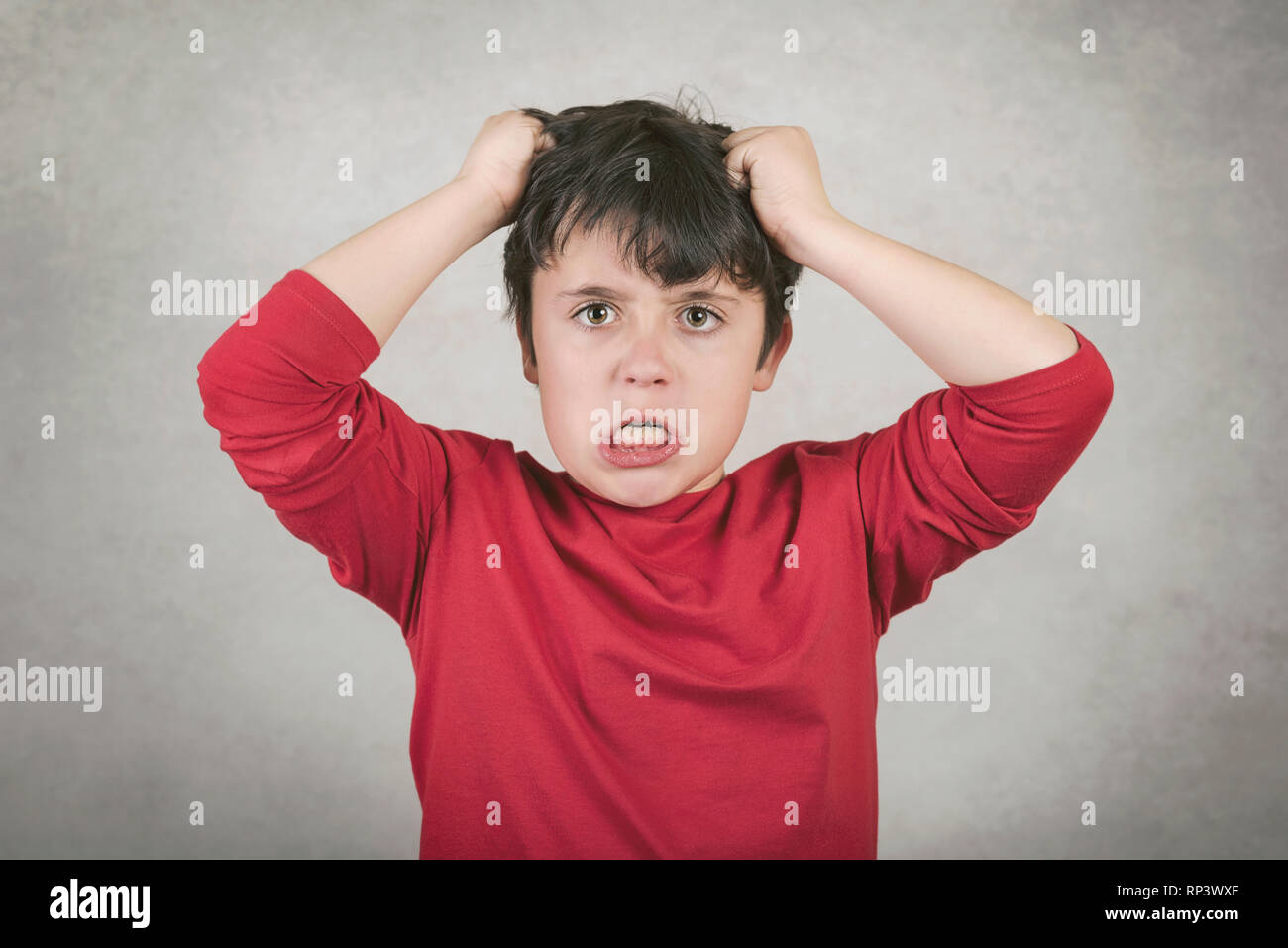 angry boy who pulls his hair against gray background - Stock Image