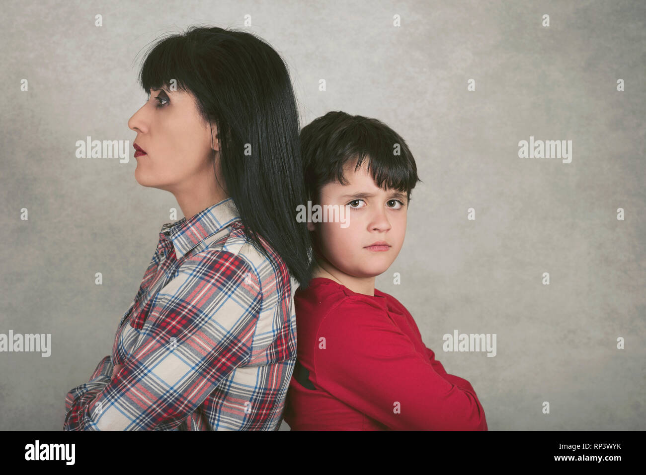 mother and son who are angry against gray background - Stock Image