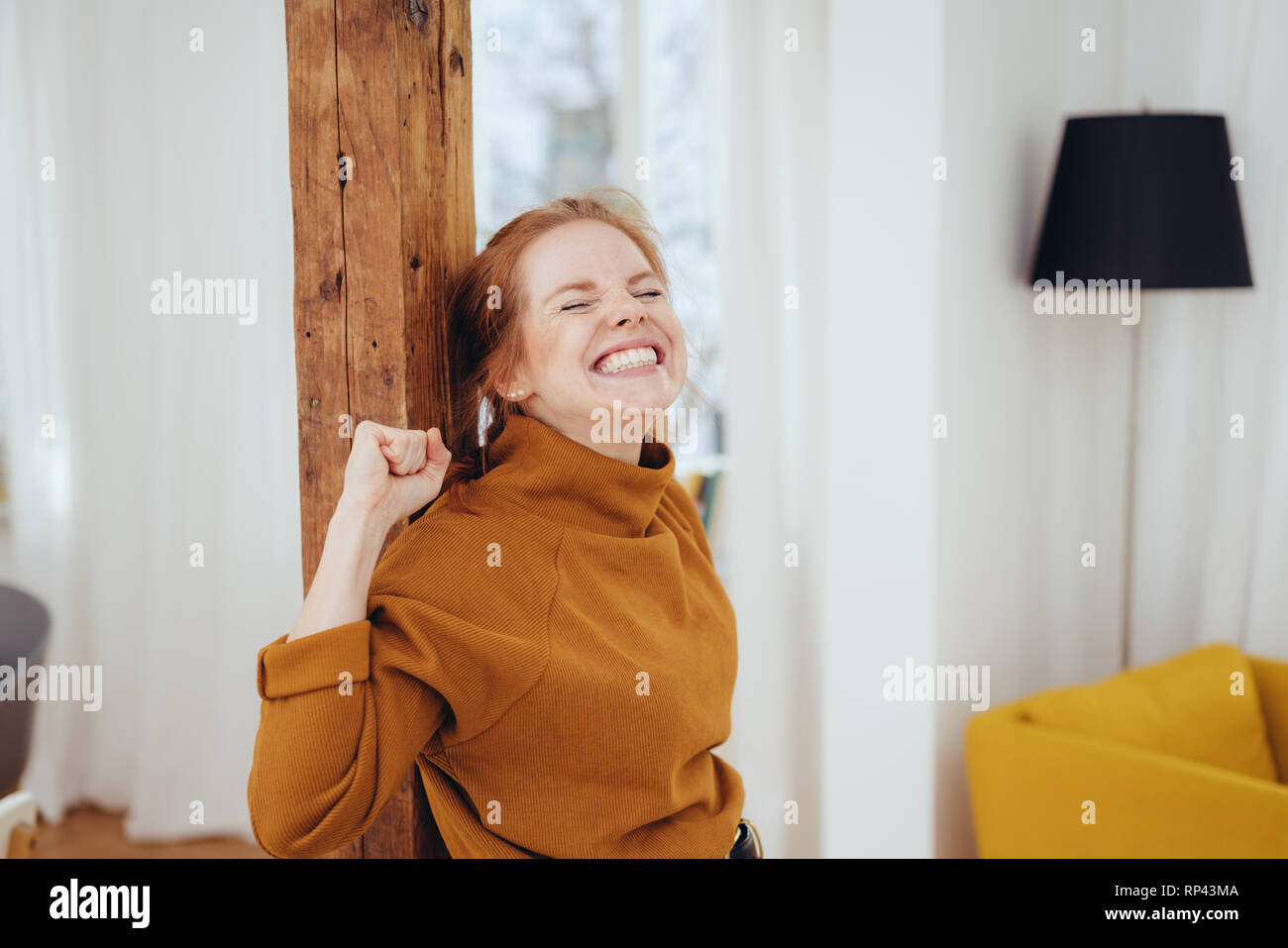 Excited young woman cheering with closed eyes and a big toothy grin clenching her fists in ecstasy as she leans on a wooden indoor pillar in her apart - Stock Image