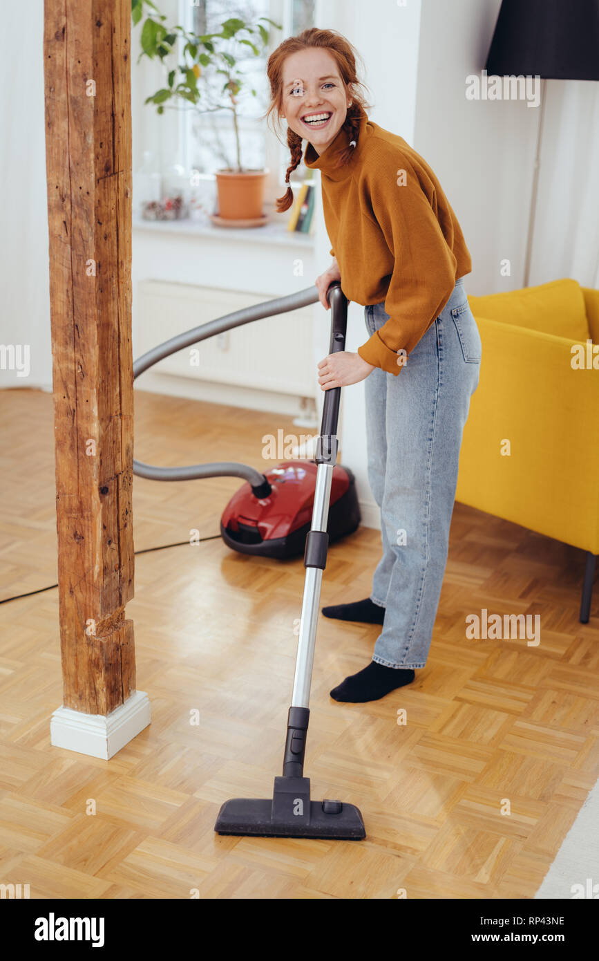 ddce190ae080 Happy red-hared girl in orange sweater and blue jeans cleaning parquet  floor in house room with vacuum cleaner