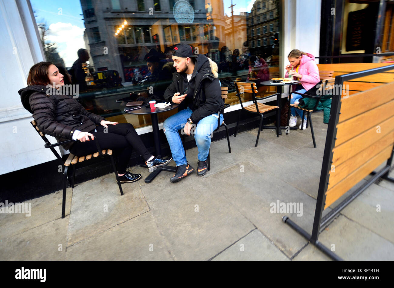 London, England, UK. Young couple drinking coffee and talking outside a cafe - Stock Image