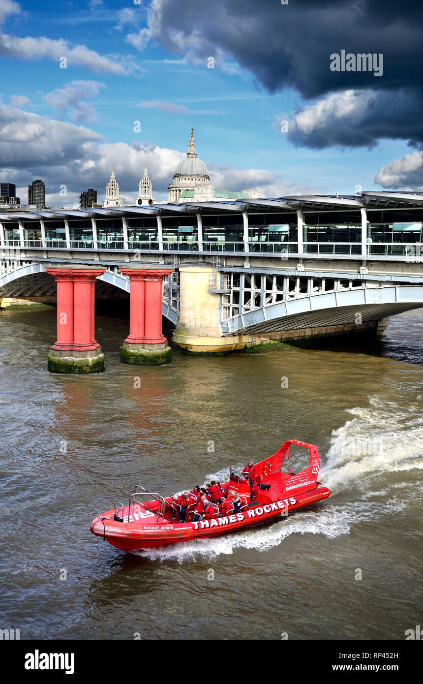 London, England, UK. Thames Rockets tourist speedboat on the River Thames passing under Blackfriars Bridge, St Paul's Cathedral in the background - Stock Image