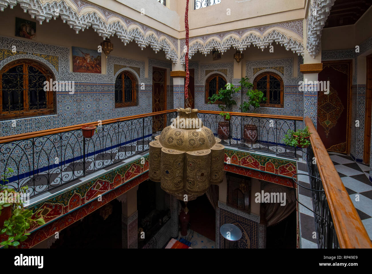 Inner courtyard with tiled walls and floor from mosaic. Traditional ornate and colorful arabesque wall carvings above an archway in Moroccan riad Stock Photo